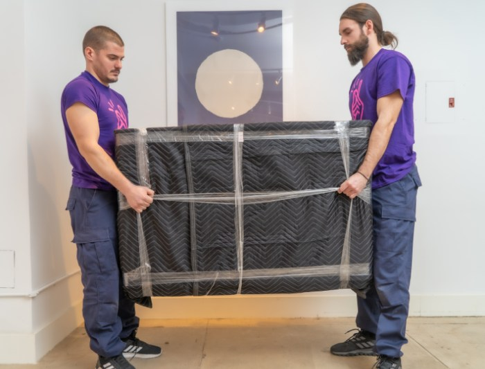 Professional movers moving heavy furniture and items